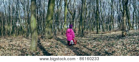 girl with a doll in the woods