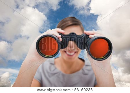 Woman looking through spyglasses against blue sky with white clouds