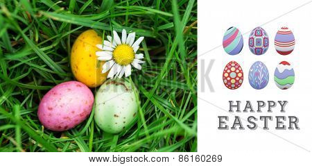 happy easter graphic against small easter eggs nestled in the grass with a daisy