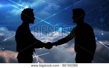 Smiling young businessmen shaking hands in office against lines against glowing sky