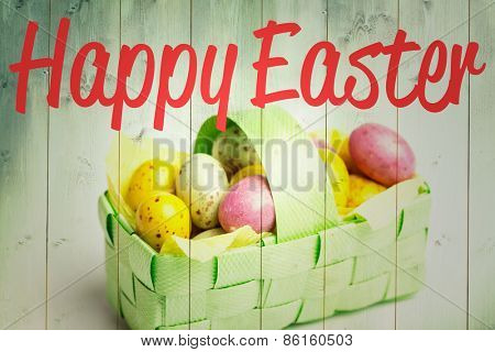 happy easter against speckled colourful easter eggs in a basket