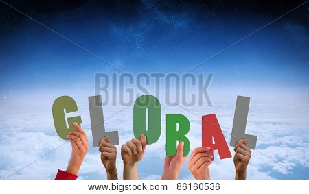 Hands showing global against white clouds under blue sky