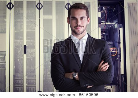 Smiling businessman posing with arms crossed against data center