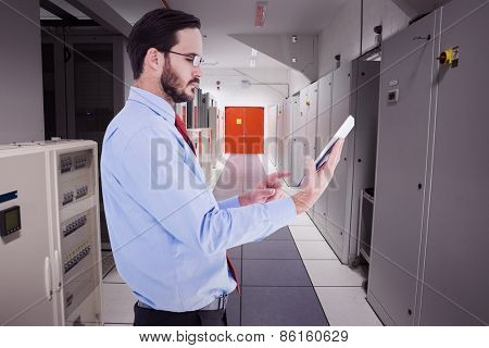 Businessman scrolling on his digital tablet against data center