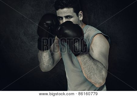 Determined male boxer focused on his training against dark background