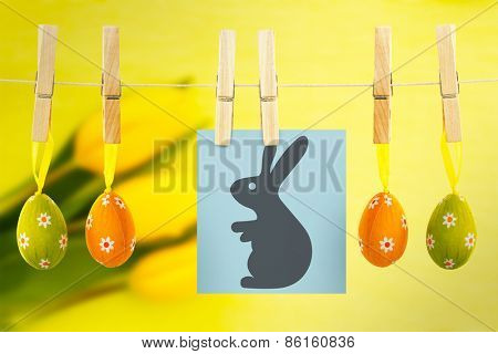 easter bunny against three yellow tulips resting on green painted background