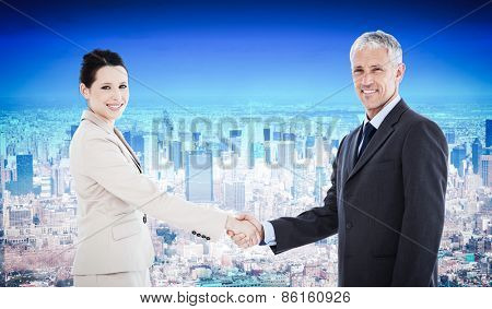 Smiling business people shaking hands while looking at the camera against new york