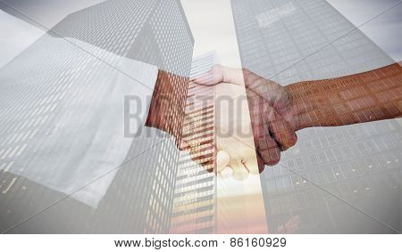 Extreme closeup of a doctor and patient shaking hands against low angle view of skyscrapers