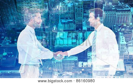 Smiling young businessmen shaking hands in office against new york