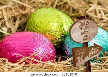 Easter egg hunt sign against three colouful easter eggs nestled in straw nest