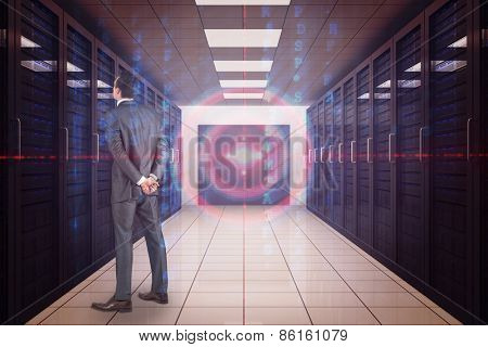 Businessman in grey suit looking against server room with towers