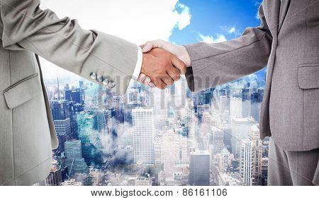 Side view of shaking hands against new york