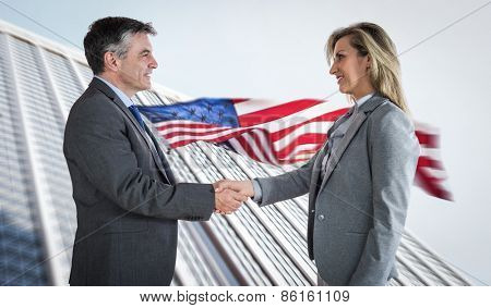 Pleased businessman shaking the hand of content businesswoman against american flag and skyscraper