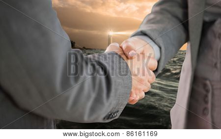 Business people shaking hands close up against stormy sea with lighthouse