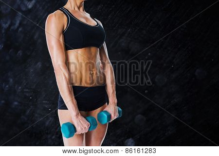 Female bodybuilder holding two dumbbells with arms down against black background