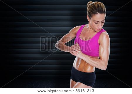 Female bodybuilder flexing with hands together against black background