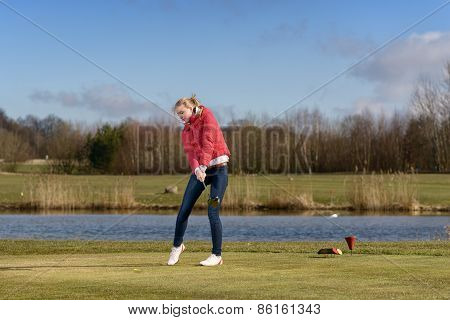 Woman Golfer Striking The Golf Ball