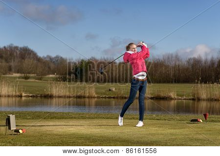 Woman Golfer Hitting A Golf Ball On The Fairway