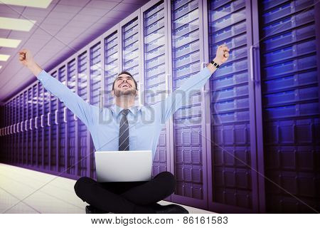 Businessman sitting on the floor cheering against server room