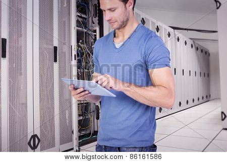 Man scrolling through tablet pc against data center