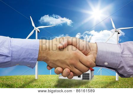 Hand shake in front of wires against house in the middle of a turbine field