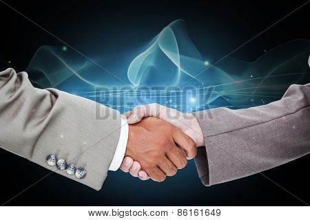 Side view of shaking hands against blue dots
