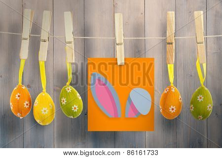 Easter bunny ears against pale grey wooden planks