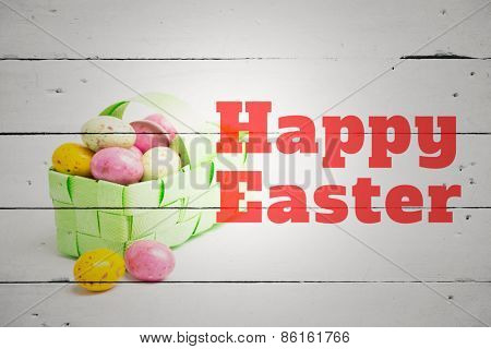 happy easter against colourful easter eggs in a green wicker basket