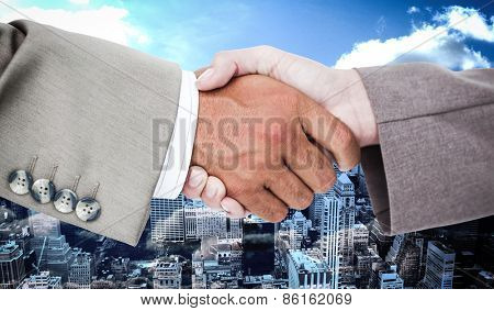 Side view of business peoples hands shaking against high angle view of city