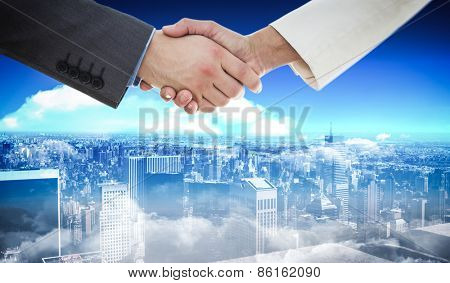 Shaking hands against high angle view of city skyline