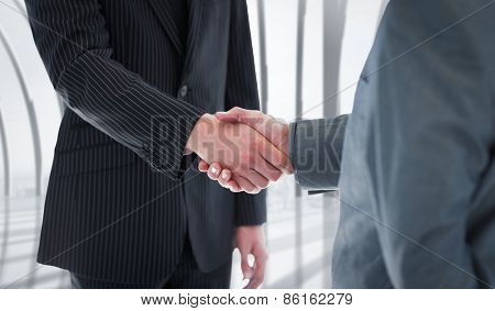 Business people shaking hands against white room with large window overlooking city