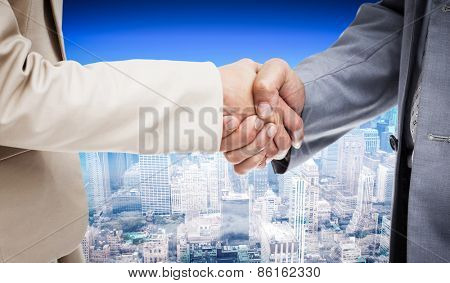 Close up of people shaking hands against city skyline