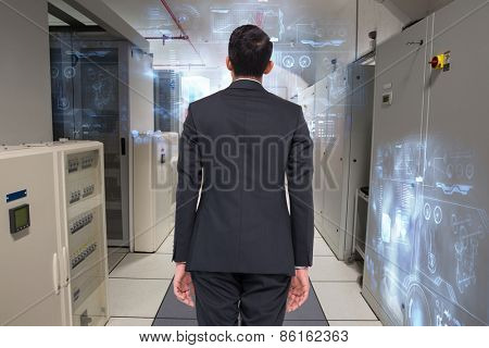 Businessman turning his back to camera against data center