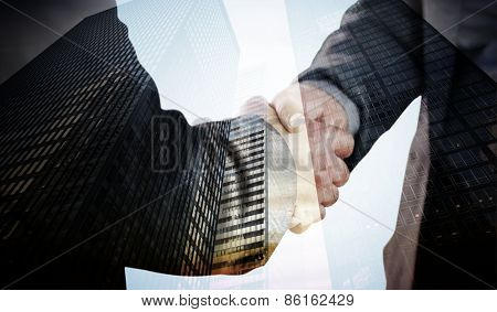 Business people shaking hands close up against low angle view of skyscrapers