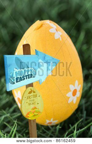 Easter egg hunt sign against yellow foil wrapped easter egg