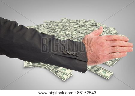 Businessman reaching hand out against pile of dollars