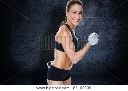 Female bodybuilder working out with large dumbbells smiling at camera against black background