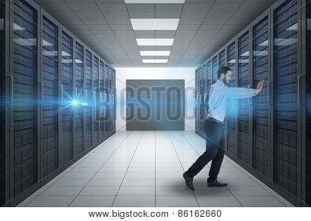 Businessman in suit pushing with effort against server hallway