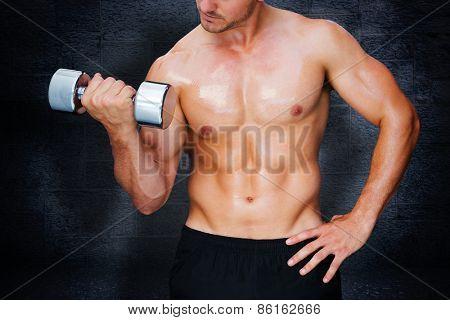 Bodybuilder lifting dumbbell against black background