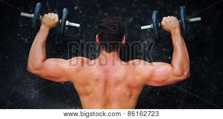 Bodybuilder lifting dumbbells against black background