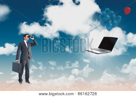 Businessman looking through binoculars against blue sky