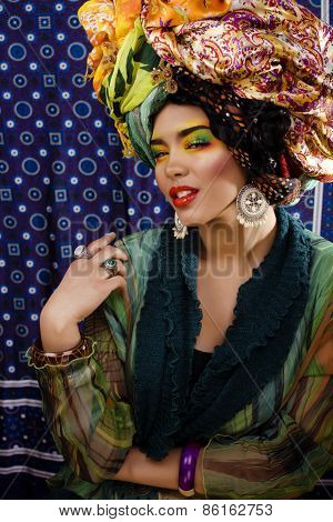 beauty bright woman with creative make up, many shawls on head