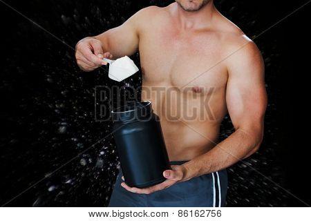Bodybuilder with protein powder against black background