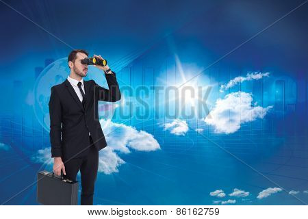 Businessman holding a briefcase while using binoculars against global business graphic in blue