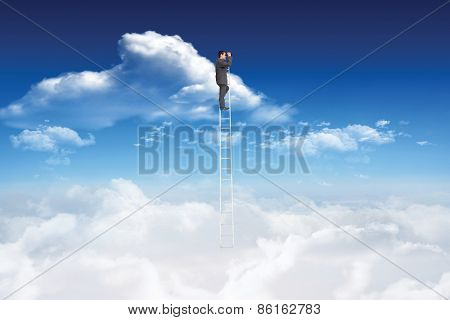 Businessman standing on ladder using binoculars against bright blue sky with clouds