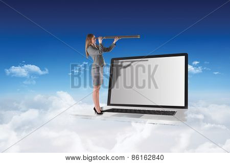 Businesswoman looking through a telescope against bright blue sky over clouds
