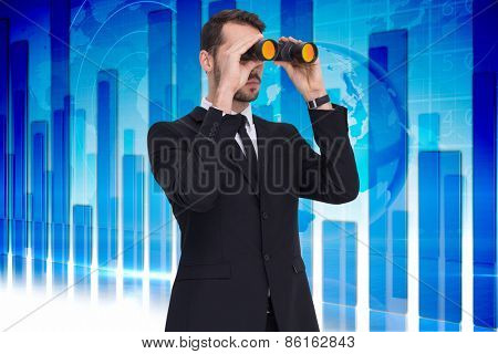 Elegant businessman standing and using binoculars against global business graphic in blue