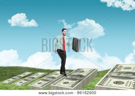 Businessman walking while holding briefcase against field and sky