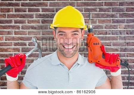 Happy repairman holding hammer and drill machine against red brick wall