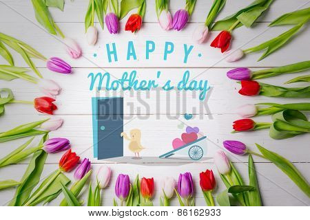 Chick with wheelbarrow of hearts against tulips on table